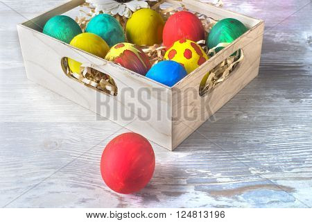 box with Easter eggs on a light wooden background
