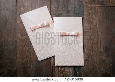 handmade card with embossed details and pink bow on wood background