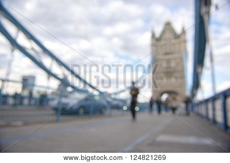 Out-of-focus image of unrecognisable pedestrians crossing Tower Bridge.