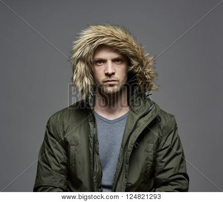 Studio portrait of young adult caucasian model wearing winter coat with hood on. Isolated on gray background.