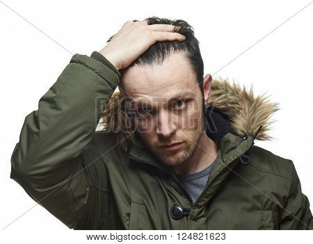 High key studio portrait of young adult caucasian model wearing hooded winter coat running fingers through his hair.