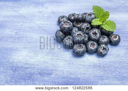 Fresh blueberries and mint leaf on rustic textured background with copy space