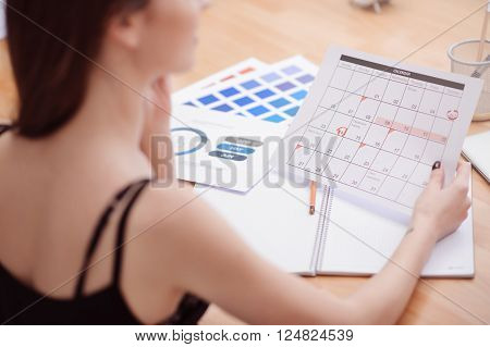 Diligent worker. Pleasant young woman sitting at the table and holding calendar while being involved in work