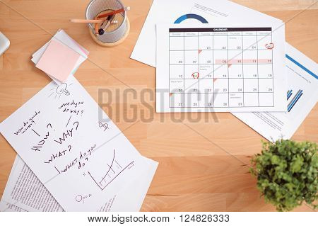 Busy tempo of life. Top view of sheets of paper lying on the surface of table