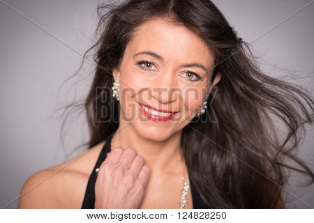 Middle aged woman with evening dress in front grey background