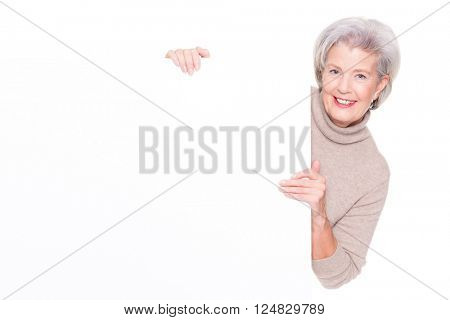 Senior woman with blank sign in front of white background