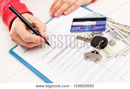 Young female leasing consultant signing car insurance contract in the office. Closeup of sold vehicle key with credit card and cash. Shallow depth of field.