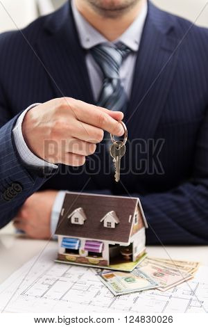 Young businessman broker offering house for rent holding keyring. Closeup of male real estate agent sitting in the office with building model on desk.