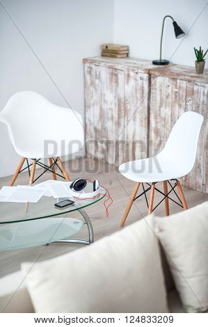 Cozy corner. View of white specious comfortable flat with chairs standing around glass table