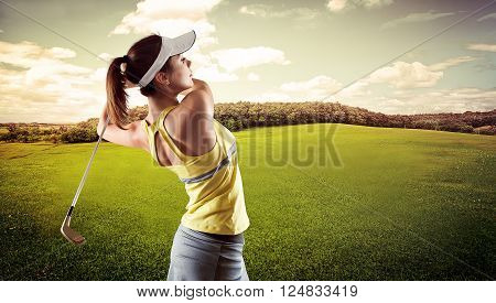 Portrait of energetic Caucasian girl doing swing on course at the summer. Focused woman with driver playing luxury game.