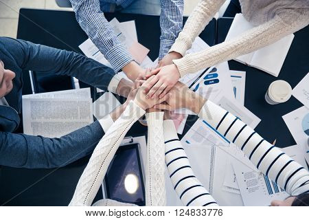 We are the one. Top  view of friendly pleasant team holding their hands on each other while sitting at the table and discussing the project