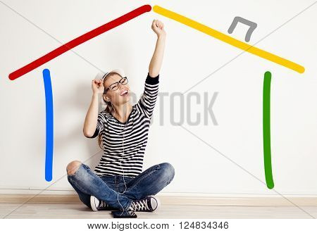 Young happy woman dreaming of new home sitting on the floor at empty wall with drawn house.