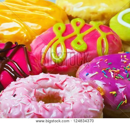 Colorful delicious donuts background. Focus on foreground