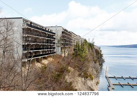 Color DSLR image of apartment or condominium building on a cliff overlooking a lake.  Horizontal with copy space for text