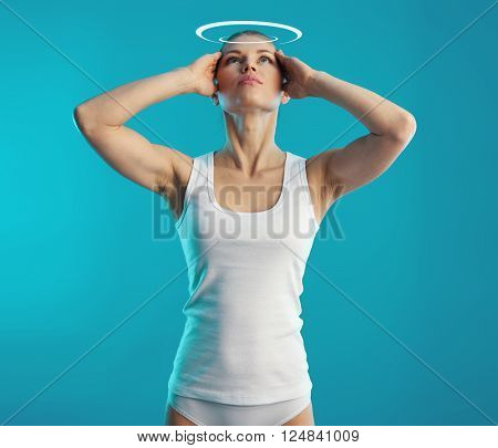 Woman suffering from vertigo and dizziness over blue background. Young female touching her head in pain. Concept of health diagnosis and treatment.