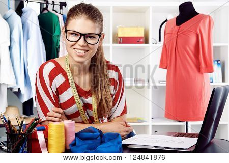 Happy woman tailor sitting with laptop at the desk in fashion studio. Stylist service concept.