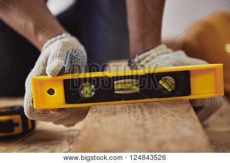 Male carver checking level of wooden plank in his shop. Construction concept.