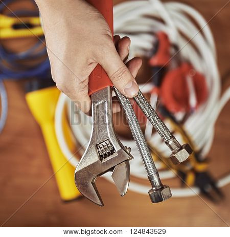 Plumber hand holding instruments. Male builder ready to install faucet in a kitchen.