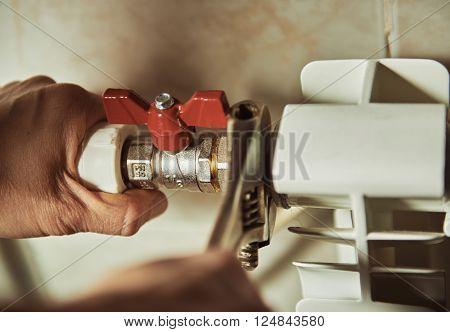Close-up of mature mechanic hands repairing heating system.