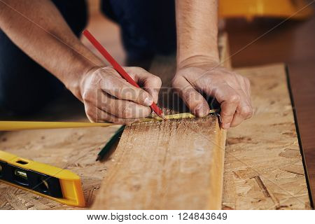 Craftsman measuring wooden plank with ruler on the floor. Concept of diy, woodworking and home renovation. poster