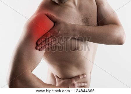 Shoulder joint fracture. Young man having rheumatism problem, touching his arm in pain.