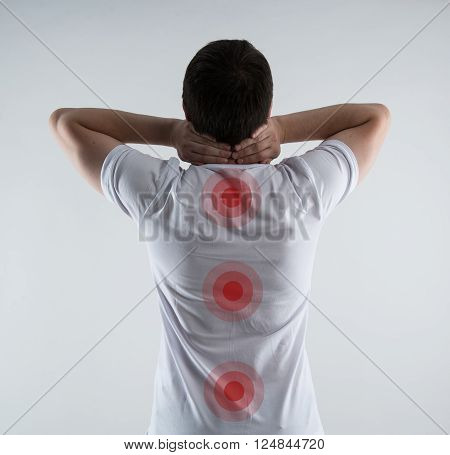 Spinal cord problem. Closeup of male back with red points on spine. Physiotherapy concept.