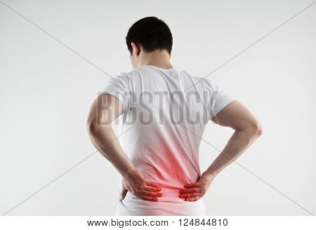 Lumbago symptom. Young man holding his painful inflamed loin. Health care and medicine. poster