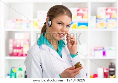 Female druggist consulting customer on phone in pharmacy. Young pretty drug store worker holding bottle with pills.
