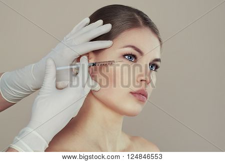 Pretty Caucasian female having injection in eyes zone. Male doctor with syringe filling woman's face with collagen. Rejuvenation therapy concept.