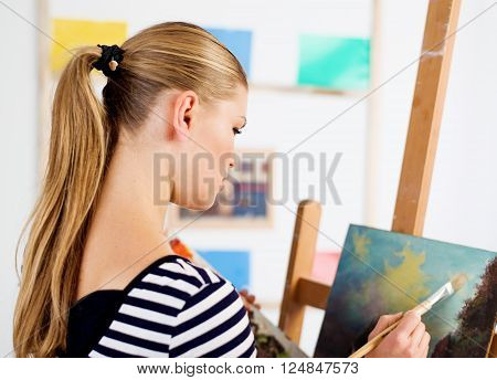 Woman painter creating new artwork in her artistic studio. Young female artist drawing oil picture of landscape.