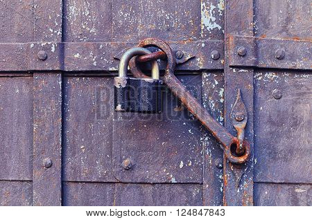 Industrial background - iron old padlock keeping the aged door heck at the rusty riveted door. Selective focus at the padlock and door heck.