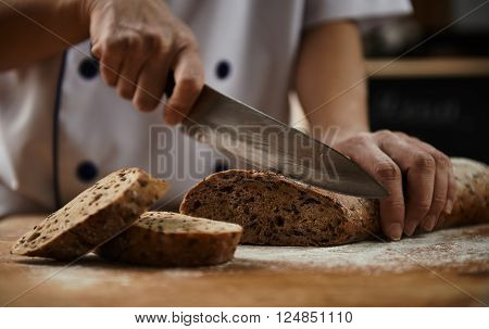 Woman chef cutting healthy bread with seeds on wooden board. Bakehouse. Bread production.