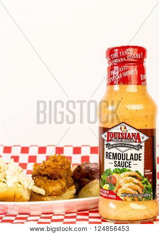 LLANO TX - APR 6 2016: Bottle of Louisiana Fish Fry Products Remoulade Sauce with Shrimp Po Boy Sandwich on red plaid tablecloth with copy space.