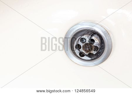 Bunch of hair trapped at bathroom wash basin drain outlet poster