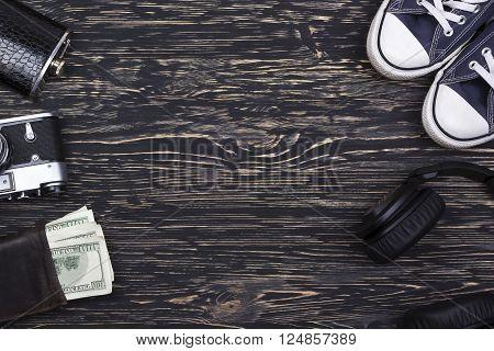 Men's accessories: wallet, headphones, flask, camera and  sneakers on wooden background