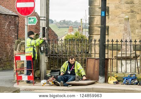 WREXHAM, WALES, UNITED KINGDOM - MARCH 21, 2016: Openreach workers fixing BT (British Telecom) telephone line outside in the street.