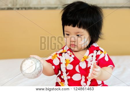 dorable Asian child girl wearing flower shirt to celebrate Thai new year, Songkran or water festival