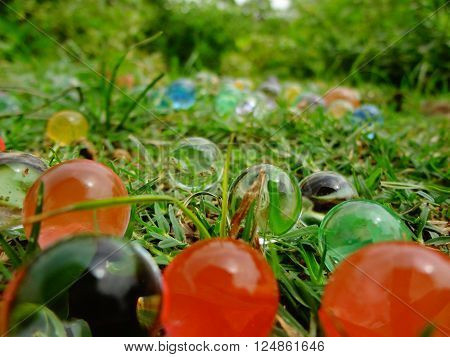 Magic balls looking like bubbles or marbles lying on grassland.