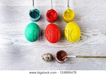 Easter colored eggs and paint on a light wooden background top view