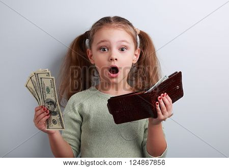 Cute Surprising Kid Girl Holding Wallet And Dollars With Open Mouth And Think How Can To Spend So Mu