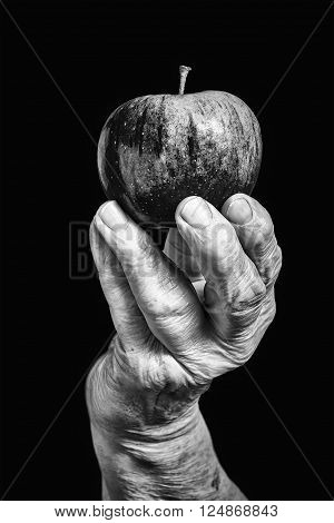 Old hand holding an apple on black background