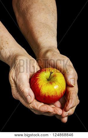 Old hands holding an apple on black background