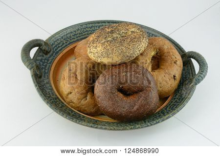 Variety of bagels on plate including poppy seed, pumpernickel, raisin and whole wheat
