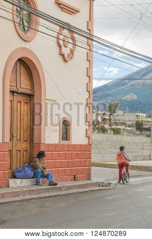 OTAVALO, ECUADOR,  OCTOBER - 2015 - Indigenous man sitting on trocal de la sierra street in the road towards San Pablo lake in the outsides of Otavalo city in Ecuador