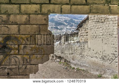 Close up view of broken brick wall and poor houses at background in a village outsides Otavalo city in Ecuador.