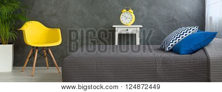 Panorama of a modern bedroom with large, yellow alarm clock on a nightstand beside a grey-covered bed