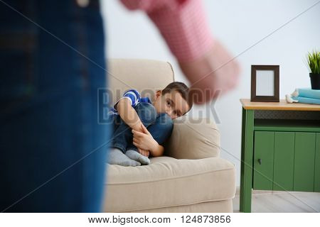 Father fist as punishment and little boy lying on sofa indoors