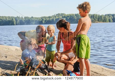 Family with four children grilling sausages over a camp fire beside a lake. The sausages are stuck onto wooden steaks gathered from the forest. Dad pretends to take youngest son's sausage. There's moke from the fire.