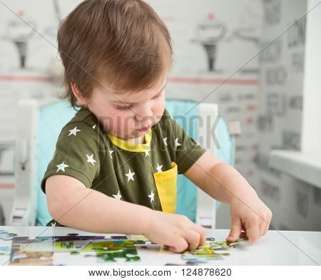 Cute 2-year old boy or toddler playing with a puzzle child development concept