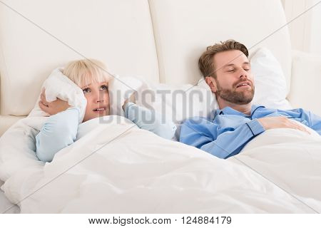 Young Woman Covering Ears While Man Snoring In Bed At Home